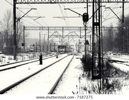Railway track with train in winter. Black and white - stock photo