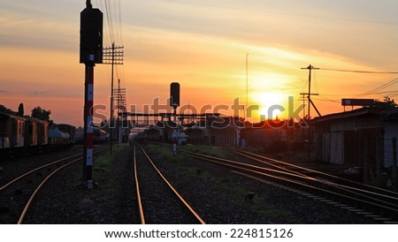 Railway Tracks at Train Station at sunset and twilight sky - stock photo