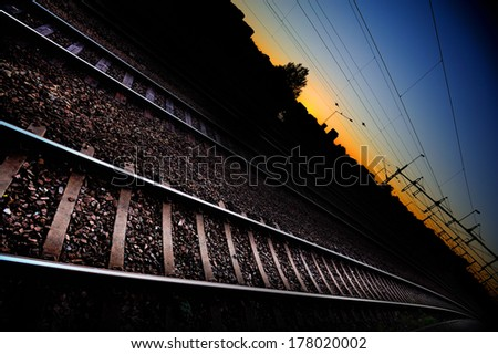 Railway tracks in sunset, city silhouette - stock photo