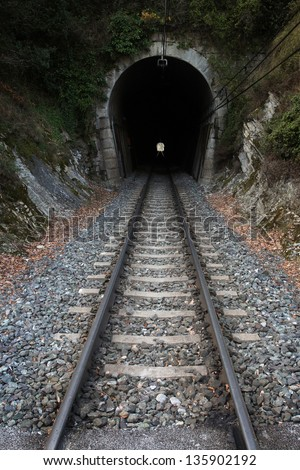 Railway tunnel. Railroad track entering in a dark tunnel