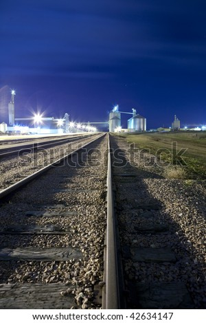 railyard and silo at night with room for copy - stock photo