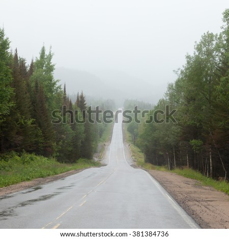 Rain and fog over Trans-Labrador Highway in Quebec, Canada. This remote road connects over more than 1100 km Quebec with Newfoundland Labrador City, Red Bay, Cartwright and Happy Valley Goose Bay - stock photo