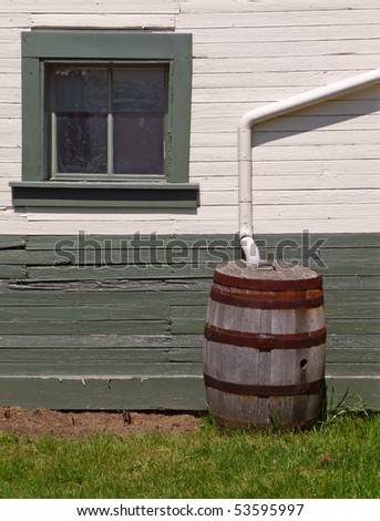 Rain barrel beside nineteenth century building - stock photo