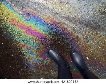 Rain boots on oil spill - stock photo