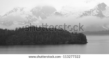 Rain clouds are low and cover the large Alaskan mountain range near College Fjord
