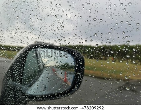 Rain drop on the mirror of a car and traffic cone on the road