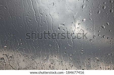 Rain droplets on a window glass pane with dark stormy clouds in the background.  - stock photo