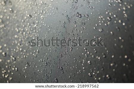 Rain droplets on black surface metal - stock photo