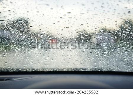 rain droplets on car windshield, blocked traffic - stock photo