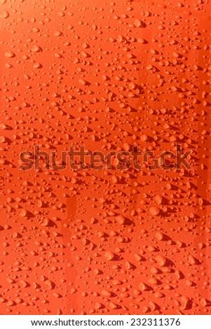 Rain droplets on orange surface metal - stock photo