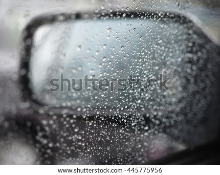 rain drops and car lights reflections through rear view mirror. summer day. Water drops on a car window - stock photo