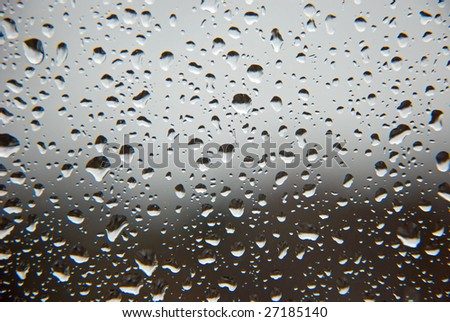 Rain drops on a window glass, with un-sharpen clouds and forest in the background. - stock photo