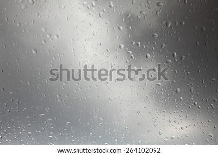 Rain drops on a windshield against a dark stormy cloud in the background.  - stock photo