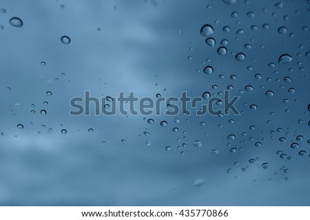 rain drops on glass. black cloud background, view in car