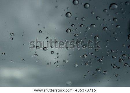 rain drops on glass. black cloud background, view in car - stock photo