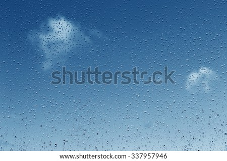 Rain drops on glass. Blue sky