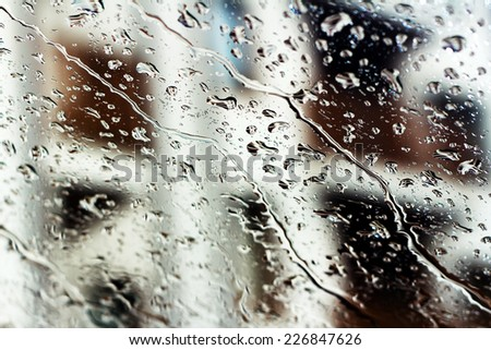 Rain drops on glass with a background. - stock photo