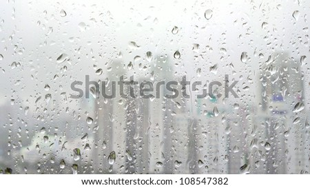 rain drops on glass with city background - stock photo