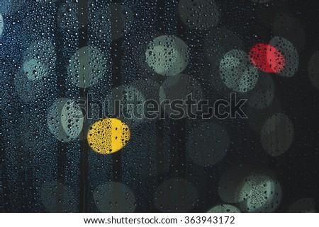 Rain drops on the window, and defocused city lights, focus on drops  - stock photo