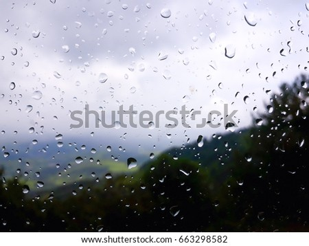 Rain drops on the window with blurred natural background in mountains space for your text