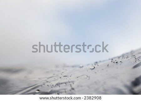 Rain drops on top of an umbrella.  A bit of the clearing sky shows above the umbrella surface. - stock photo
