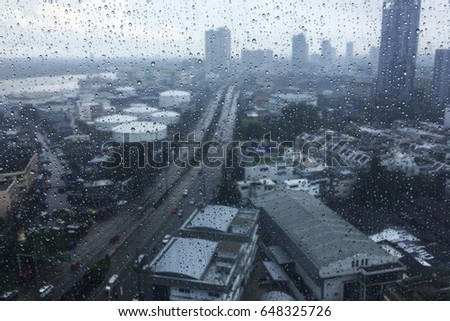 Rain drops on  window glass from top view with city background outside in Bangkok