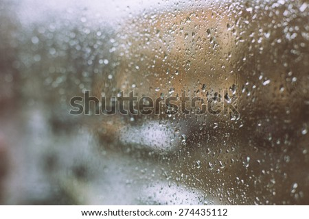 rain drops on window retro filter city background - stock photo