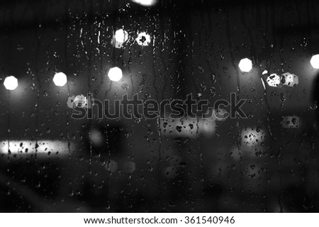 Rain drops on window with street bokeh lights - stock photo