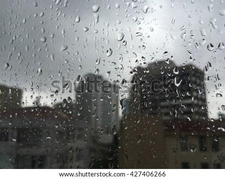 rain drops on windowpane against buildings - stock photo