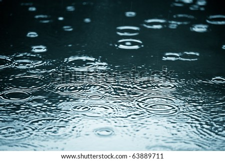 Rain drops rippling in a puddle with blue sky reflection - stock photo