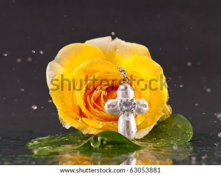 Rain Falling Down on Yellow Rose with Small Baptism Cross - stock photo
