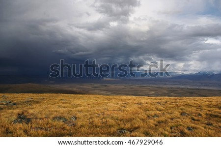 Rain from the storm dramatic dark scary clouds and a highland bright steppe with dry yellow grass Plateau Ukok Altai mountains, Siberia, Russia