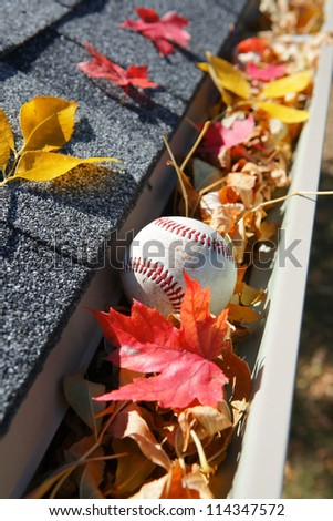 Rain gutter full of autumn leaves and a baseball - stock photo