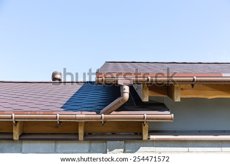 Rain gutter system on a roof of home against blue sky - stock photo