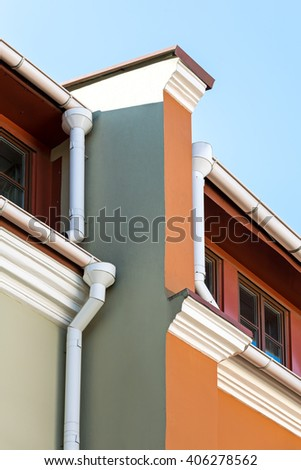 rain gutter system with drainpipe on red wall old building - stock photo