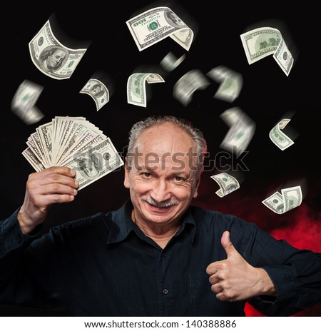 Rain of dollar bills. Lucky old man holding with pleasure group of dollar bills