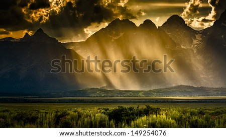 Rain, ominous clouds, and sunshine over the Teton peaks in Wyoming