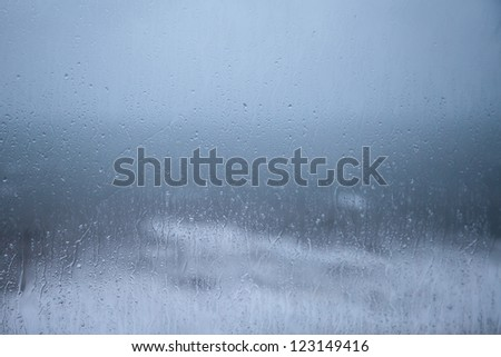 Rain on ruined holiday?! Horrible rain & weather forecast! Rain drops on window pane, blurry, wet. Stormy sea, rain & cloud in background, themes of staying indoors on a boring rainy day / holiday. - stock photo