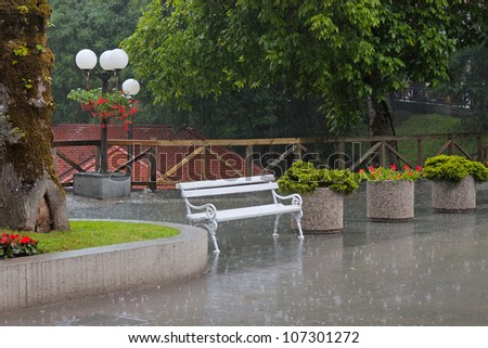 Rain on the street with a bench, flowers, lanterns.