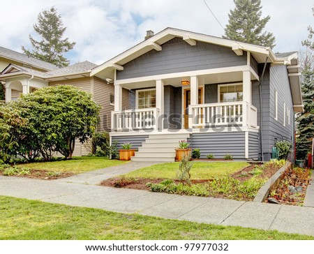Rain-streaked bue grey small craftsman style house with white porch. - stock photo