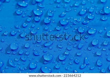 Rain Water droplets on blue fiber waterproof fabric - stock photo
