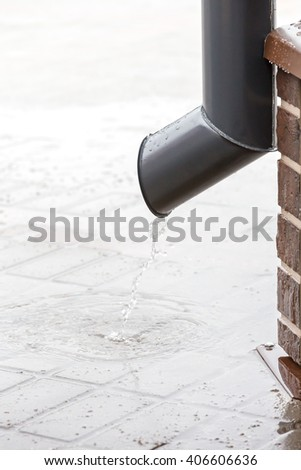 rain water flow from drainpipe on the pavement  - stock photo
