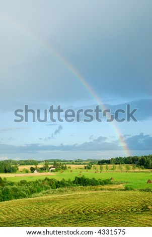 Rainbow above a field - stock photo
