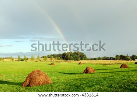 Rainbow above a rural field - stock photo