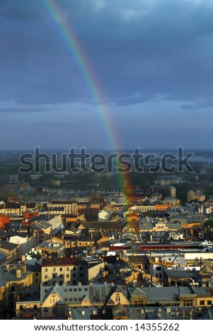Rainbow above old european city roofs, dark clouds at background. - stock photo