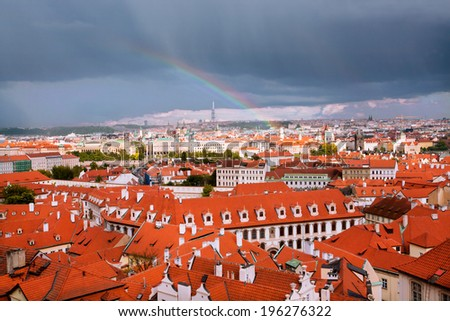 Rainbow after the rain rises above the old roofs of Prague - stock photo