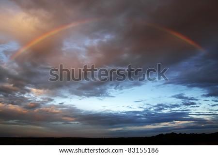 Rainbow against a dark sky at sunset - stock photo
