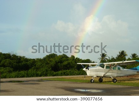 Rainbow and Airplane after Downpour An airplane reposes under a gorgeous double rainbow at Dangriga Airport, Belize. Taken shortly after a morning rain. - stock photo