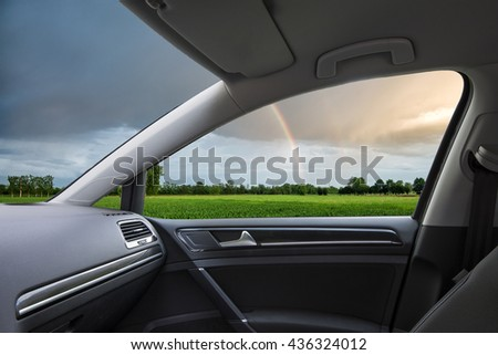 Rainbow at sunset over a field seen from inside a car