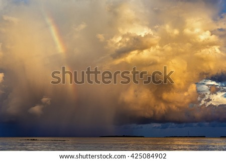 rainbow beautiful seaside at the time of sunset, storm clouds - stock photo